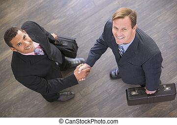 deux, intérieur, hommes affaires, mains, sourire, secousse