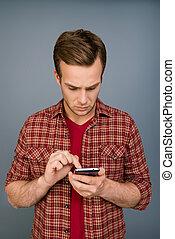 disposé, message, smartphone, homme, dactylographie, jeune, sérieux