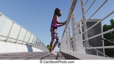 elle, jambe, balustrade, pont, femme américaine, africaine, tenue, ville, étirage