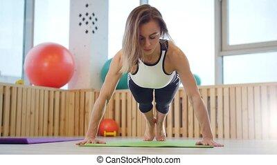 entraîneur, femme, jeune, studio, fitness, poussée, augmente