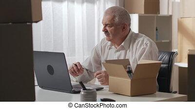 envoyé, blanc, table, être, chemise, chèques, homme, laptop., client, assied, entrepôt, ménage, chemicals., gray-haired, ordre, travail, utilisation