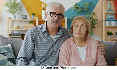 faces, étreindre, sérieux, couple, maison, regarder, mûrir, portrait, appareil photo, adultes