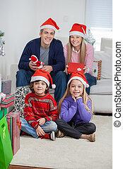 famille, chapeaux, santa, pendant, maison, noël