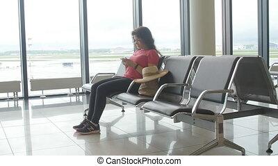femme, attente, jeune regarder, aéroport, smartphone, départ