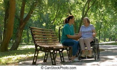 femme, fauteuil roulant, handicapé, conversation, dehors, personne agee, caregiver