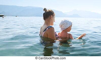 femme heureuse, elle, jeune, fils, vidéo, 4k, mer, enfantqui commence à marcher, natation