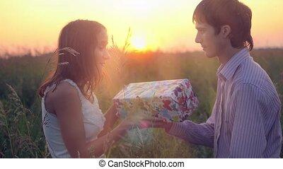 femme, hugging., amour, couple, heureux, concept., sunset., homme, boîte-cadeau, sourire, dehors, sien, lumière soleil, donner