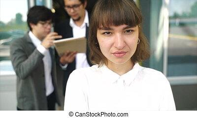 femme, jeune, beau, poser, appareil photo, deux, fond, hommes affaires