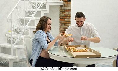 femme mange, gras, pregnant, kitchen., leur, nourritures, maison, homme pizza