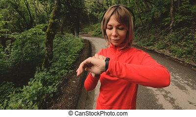 femme, paramètres, écouteurs, montre, jeune, jogging, vert, séduisant, devant, changer, psole, intelligent, ou, route, forêt