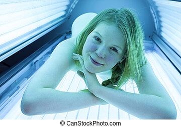 femme prendre bain soleil, solarium, lit, bronzage, apprécier