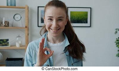 femme souriante, ok, debout, exprimer, gai, main, projection, geste, approbation, jeune, maison