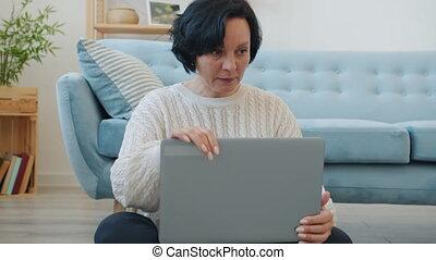 femme souriante, ordinateur portatif, alors, tourner, pensée, intérieur, utilisation, dactylographie, fermé, maison