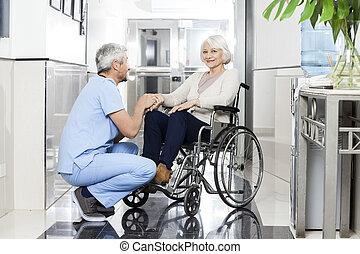 femme, tenant main, personne agee, kinésithérapeute, sourire, wheelchai