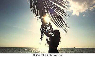 femme tropicale, feuille, soleil, motion., jeune, lentille, apprécier, clair, lent, paume, effets, flamme, sun., toucher, heureux