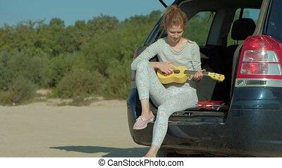 femme, ukulele, voiture, mer, coffre, ouvert, jouer