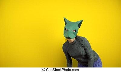 femme, vert, regarde, jeune, masque, carton, jaune, chandail, chacal, mask., arrière-plan., appareil photo