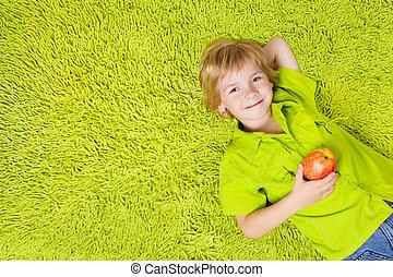 garçon, apple., regarder, fond, appareil photo, vert, enfant avoirs, sourire, mensonge, moquette