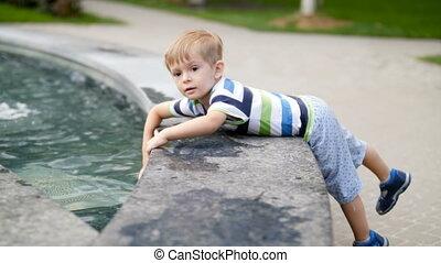garçon, mignon, métrage, parc, eau, toucher, fontaine, 4k, enfantqui commence à marcher