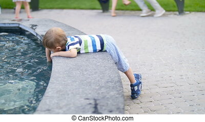 garçon, peu, métrage, parc, fontaine, 4k, enfantqui commence à marcher, jouer