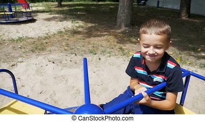 garçon, ralenti, rotation, cour de récréation, carrousel, enfant, heureux