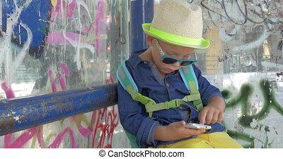 garçon, smartphone, autobus ville, arrêt, grungy