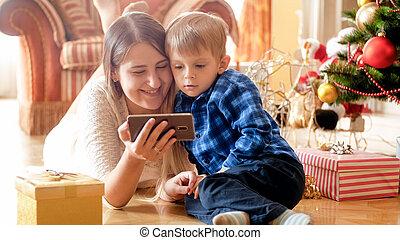 garçon, smartphone, heureux, matin, mère, portrait, utilisation, apprécier, enfantqui commence à marcher, noël