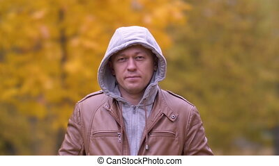 gris, debout, parc, regarder sérieux, capuchon, homme, jeune, appareil photo