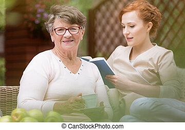 gros plan, femme, elle, facility., jeune, loisir, brouillé, personne agee, livre, patio, fond, temps, pendant, infirmière, lecture, professionnel, soin jour, heureux