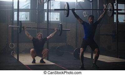 gymnase, exercices, fort, athlètes, simultaniously., motion., barbell., deux, lent, athlétique, haltérophilie, barre disques, hommes, mâle
