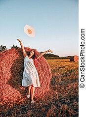 haystack., heureux, matin, meule foin, chapeau, voler, beau, cottagecore, robe, assied, portrait, jeune, lumière soleil, countryside., femme