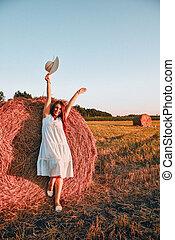 haystack., portrait, beau, countryside., robe, cottagecore, meule foin, assied, matin, chapeau, voler, lumière soleil, jeune femme, heureux