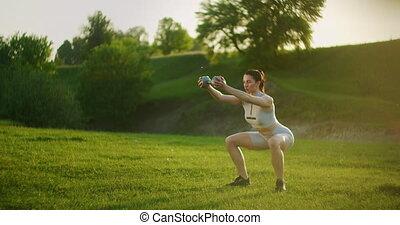 herbe, mains, dumbbells, air, jeune, formation, s'accroupit, sunset., femme, ouvert, parc, elle