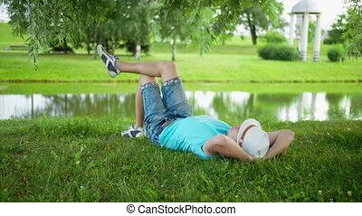 heureux, jeune, sous, parc, herbe, chapeau, ville, mensonge, reposer, arbre, homme