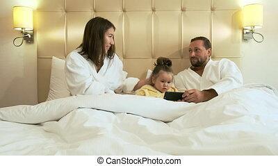 heureux, smartphone, famille, lit, hôtel, room.
