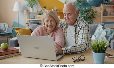 homme, écran, rire, sourire, portable utilisation, femme aînée, regarder, conversation