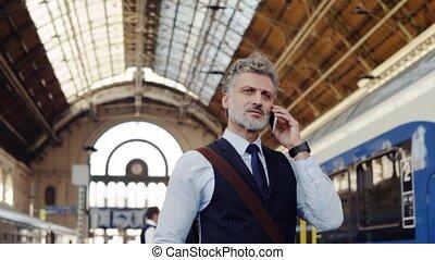 homme affaires, train, smartphone, station., mûrir