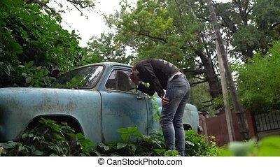 homme, voiture abandonnée, considère, vieux, envahi, végétation