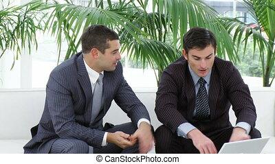 hommes affaires, ordinateur portable, sofa, utilisation, deux, séance