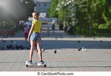 hoverboard, enfant, regarder, jour ensoleillé, tourner, girl, équitation, appareil photo