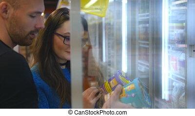 il, congélateur, choisir, crème, debout, jeune, glace, magasin, heureux, produit, couple, frigidaire, nourriture., basket., mettre, paire, store., cueillette, paquets, épicerie, surgelé, prendre
