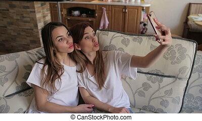 ils, prendre, filles, deux, envoyer, air, selfies, appareil-photo., divan, baiser, portrait
