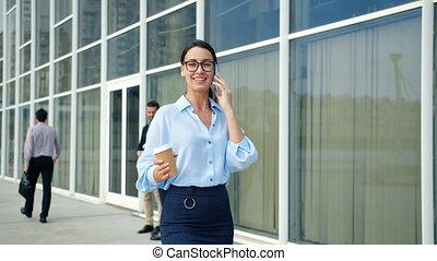 indépendant, femme souriante, marche, district, business, cellphone, ville, conversation