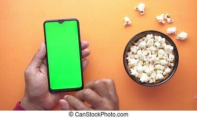 intelligent, homme, utilisation, main, pop-corn, téléphone, manger