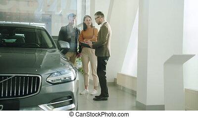 jeune, vendeur auto, famille, mari, concession, choisir, conversation, épouse, voiture, heureux