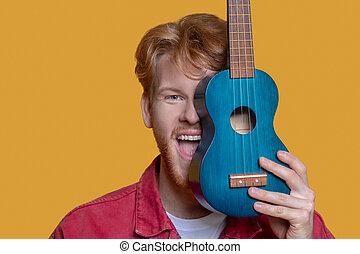 jeune, veste, beau, homme, barbu, ukulele, rouges