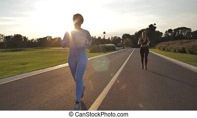 jeunes femmes, parc, course, pendant, coucher soleil, ruelle