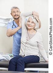 kinésithérapeute, patient, portion, personne agee, bras, exercice