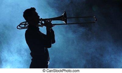 lent, silhouette, enfumé, musicien, jouer, mouvement, trombone., studio, homme
