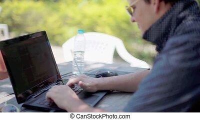 lunettes soleil, fonctionnement, arrière-plan., bois, ordinateur portable, brouillé, suivant, eau, lumières, bokeh, homme affaires, bouteille, sérieux, table, assied